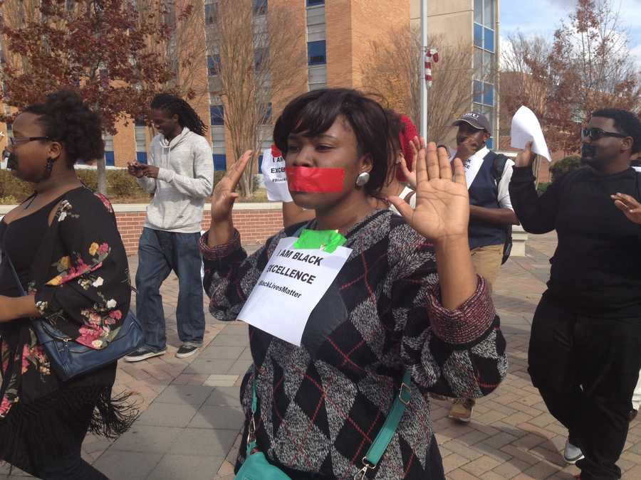 About 100 students marched down the Gibbs-Green Plaza with their hands raised and their mouths taped shut.