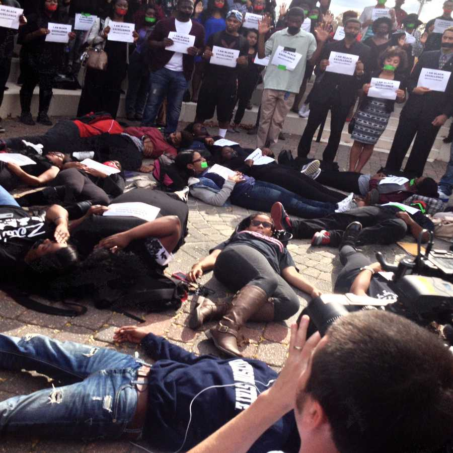 The students were lying motionless on the ground under a pavilion while others held up signs.