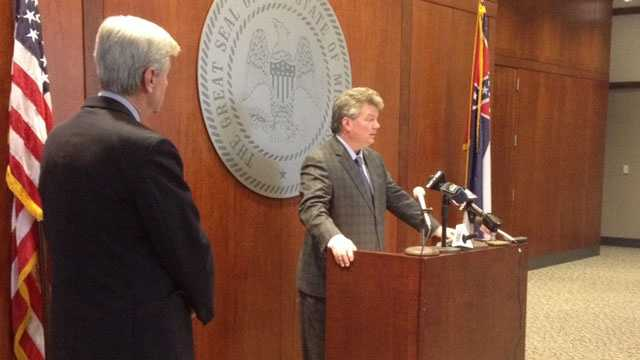 Gov. Phil Bryant stands by as Attorney General Jim Hood addresses the media.