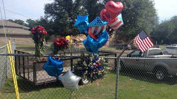 Red roses decorated a chain-link fence Sunday near the spot where officers Benjamin Deen and Liquori Tate were killed.