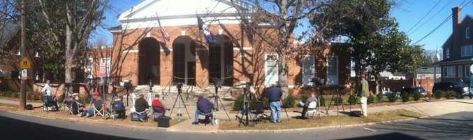On a rare Saturday session, television news photographers wait outside Charlottesville Circuit Court, at the ready for their reporters to emerge with their stories.