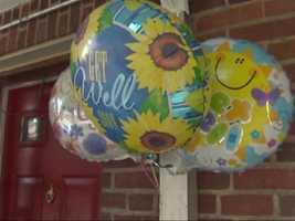 "Neighbors leave ""get well"" balloons for the children."