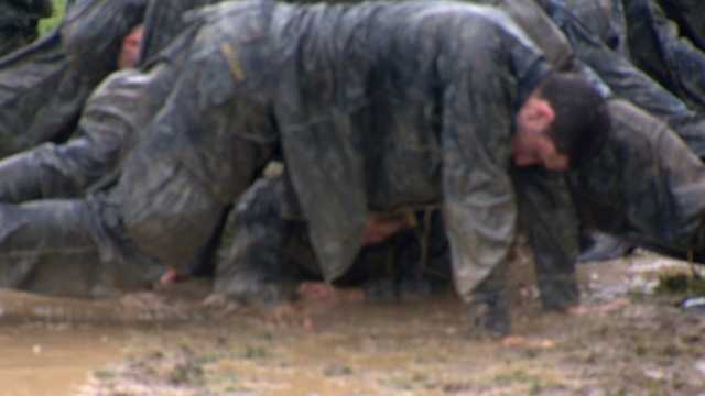 At this station, mids get down and arch their body in the mud while classmates crawl under.