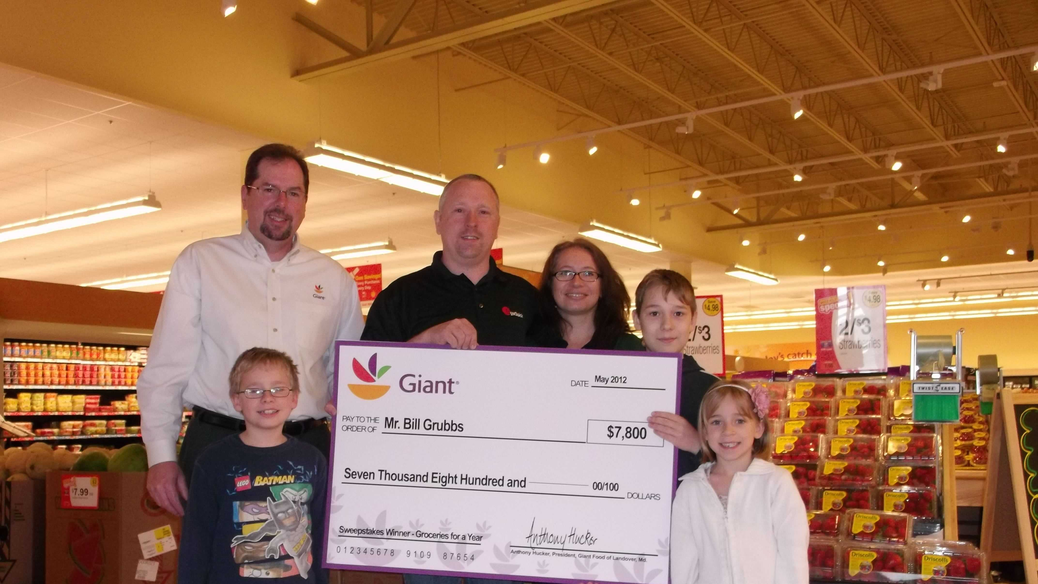 Jamie Miller (left), public and community relations manager for Giant Food of Landover, Md., presents the Year of Groceries Sweepstakes Winner Bill Grubbs with a check for $7,800 at the new Parkville Giant in Parkville, Md. Grubbs, joined by his wife and three children, will receive Giant Food gift cards, totaling $7,800 to spend on groceries at his neighborhood store.