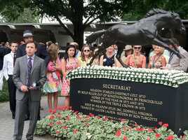 NBC Sports' Bob Costas standing next to the statue of Secretariat at Churchill Downs.