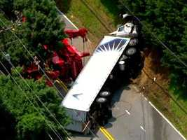 The driver of a tractor-trailer was injured Tuesday when police said he collided with another vehicle and ended up overturning the vehicle.