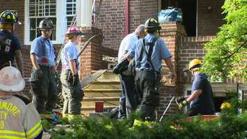 """Fire officials said they discovered the man being rescued is about 60 years old and was living illegally in the house, which has a """"for sale"""" sign on it."""