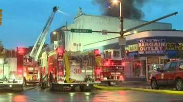 Baltimore City fire crews worked Thursday morning to put out a three-alarm blaze at a liquor store in Fells Point.