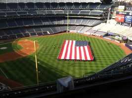 Crews rehearse unfurling the flag on the field at Yankee Stadium.