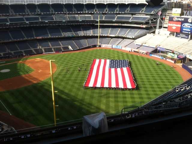 Crews rehearse unfurling the flag on the field at Yankee Stadium.