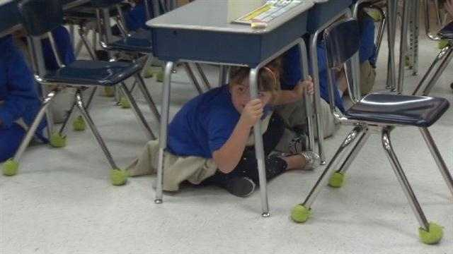 Baltimore City school students practice earthquake safety in class during a nationwide exercise.