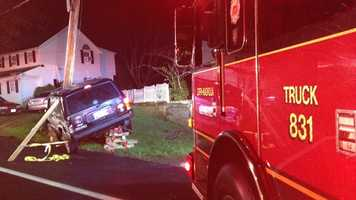 Fire crews stabilize the vehicle and the pole as crews from Baltimore Gas and Electric were called.