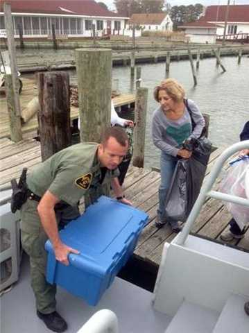 Natural Resources Police Cpl. Brimer assists a resident of Smith Island during evacuations there.