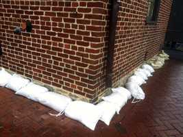 Residents and businesses lay down sandbags in preparation for the storm.