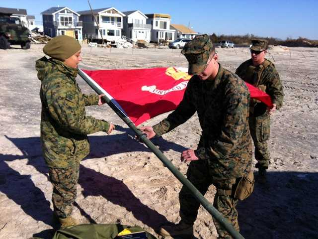 Marines from 8th Engineer Support Battalion, 2nd Marine Logistics Group raise the Marine Corps flag outside of their forward operations center at Breezy Point, N.Y., on Friday morning, taking part in the largest military presence in the neighborhood after more than 100 Marines and sailors from the 26 Marine Expeditionary Unit came ashore by landing craft.