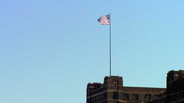 The 120-square foot American flag was raised above the building Monday morning.