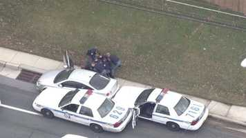 The images show officers pulling the suspect, a woman, from the vehicle.