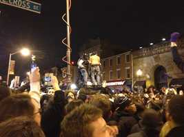 Fans in Baltimore's Federal Hill neighborhood climb on top of vehicles, including the WBAL-TV 11 News van, following the Ravens win in the Super Bowl.