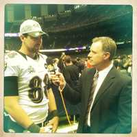Sports reporter Pete Gilbert talks with tight end Dennis Pitta.