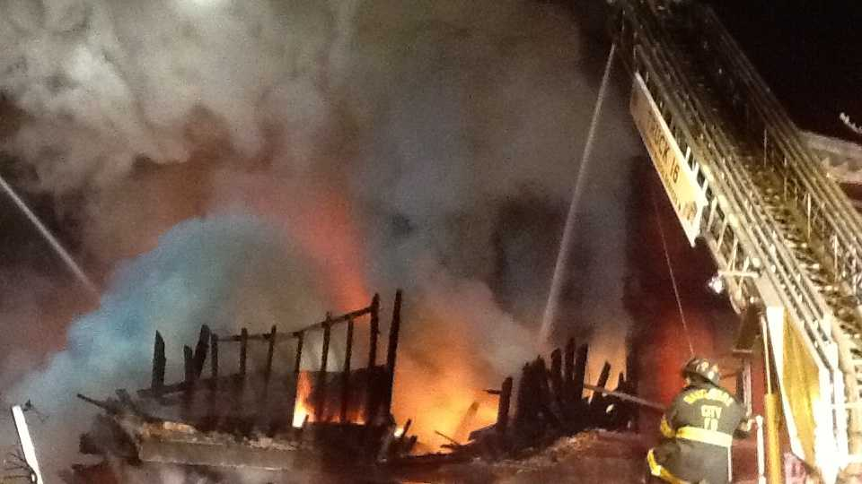 Nearly 100 firefighters battled a four-alarm blaze Monday that injured several crew members in west Baltimore.