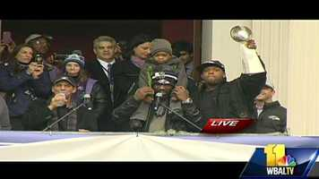 Ed Reed, with his son, entertains the crowd as Terrell Suggs holds the Lombardi Trophy.