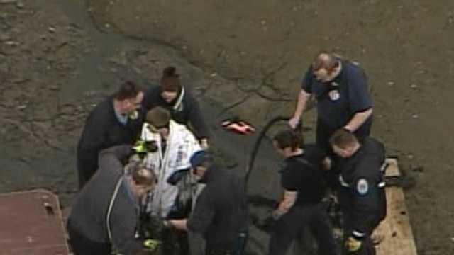 young man stuck in mud rescued