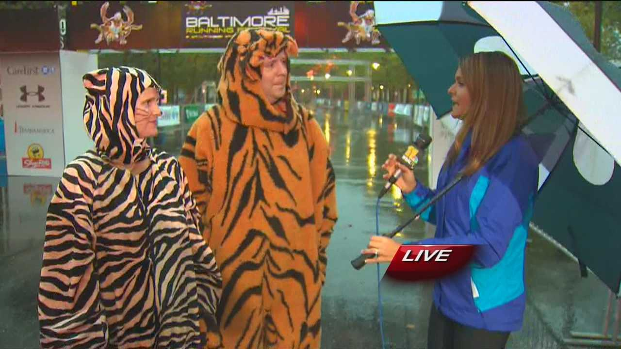 Ava Marie chats with two fur-clad Baltimore Running Festival groupies, one of which is known as the 'Eye of the Tiger Guy,' about their entertaining cheering routine put on at Mile 23 of the race at 30th Street and Guilford Avenue.