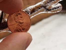 WBAL-AM radio host Phil Yacuboski measures the ice with a penny in Sparks.