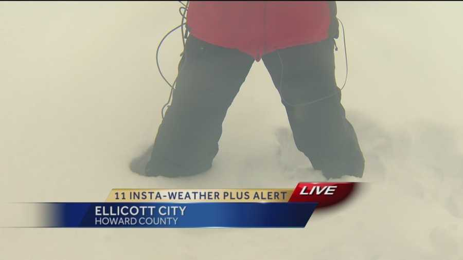 11 News reporter Kim Dacey, who admits to being short, demonstrates how high the snow is (up to her knees) along Route 40 in Ellicott City at 9 a.m. Thursday.
