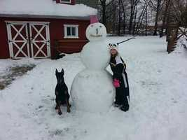 """""""This is a picture of my daughterJazzy and her Doberman dog named Titan with their snowman,"""" said June from Middle River."""