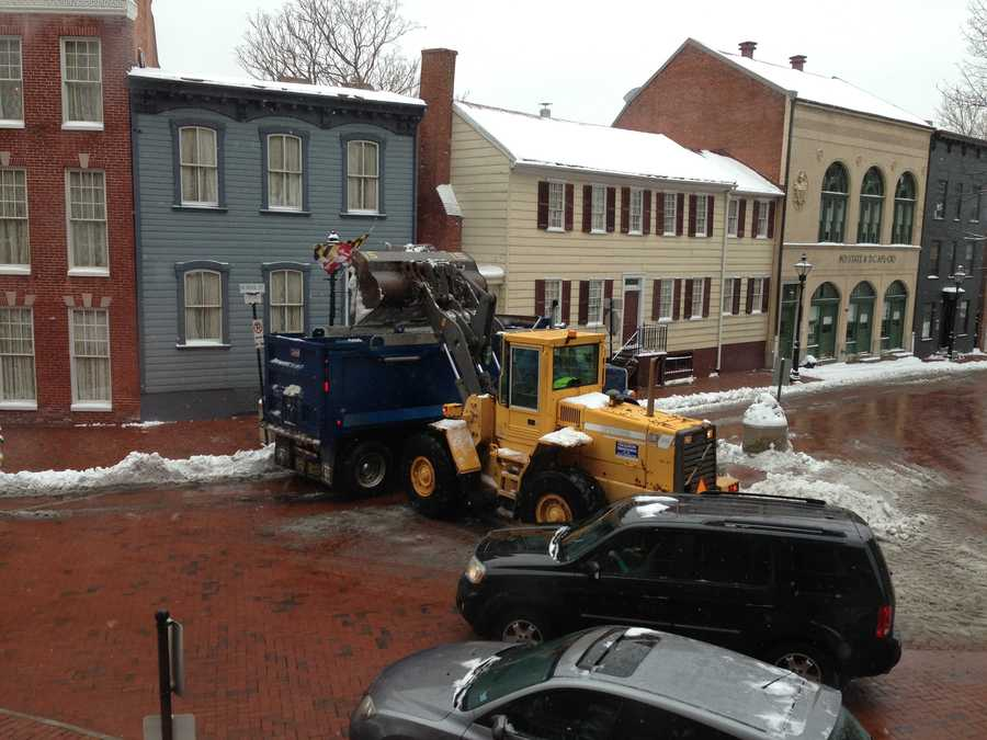 Heavy equipment used to clear snow outside state capital building.