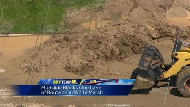 Crews could be seen at noon Thursday clearing out massive amounts of mud that streamed down a hill onto Route 43.
