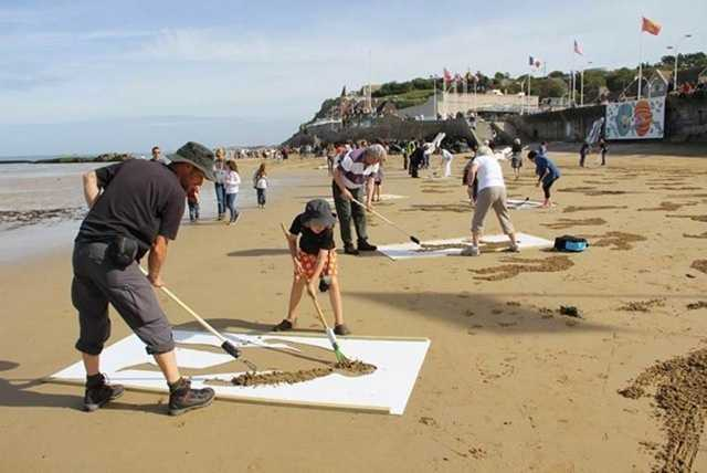 The group took to the beaches of Normandy with rakes and stencils to etch 9,000 silhouettes into the sand to represent those who died on D-Day.