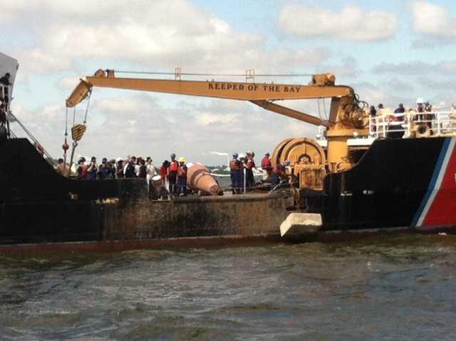 Coast Guard crew members prepare to drop the Francis Scott Key buoy into the Patapsco River.