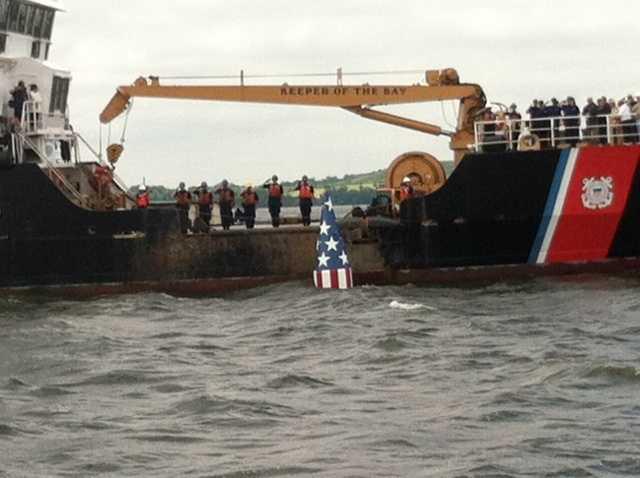 Coast Guard members salute a successful drop.