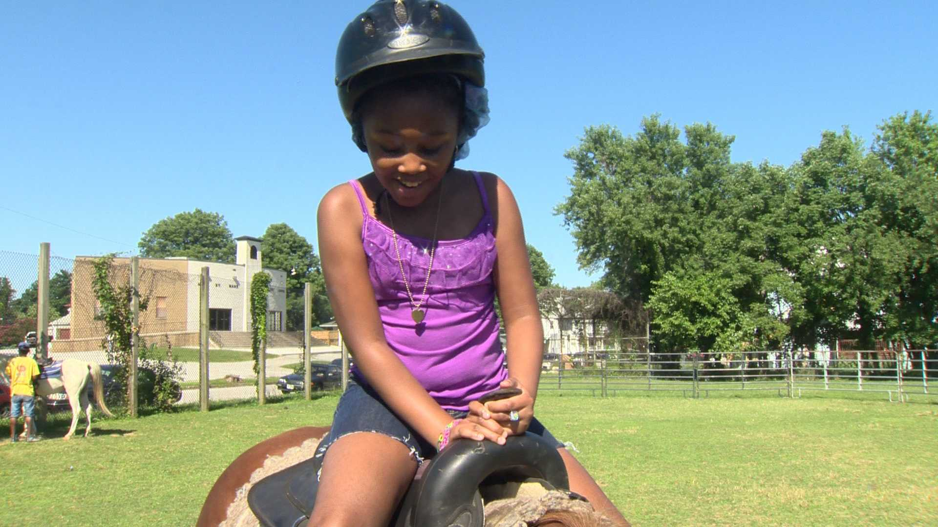 Trinity McClain smiles after she gets onto the horse.