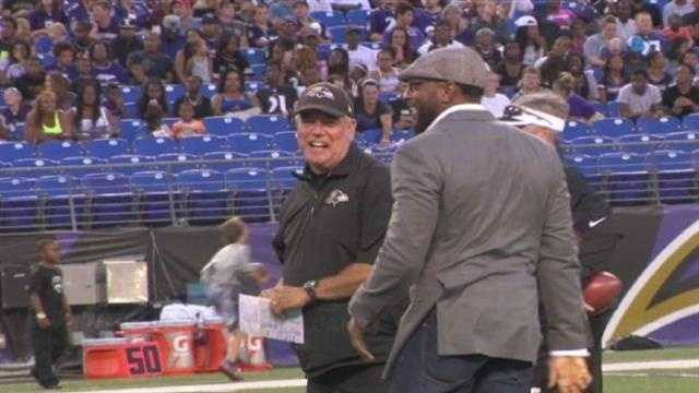 Ray Lewis greets defensive coordinator Dean Pees at he visits open practice Monday.