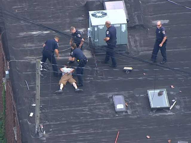Police said officers arrested the unidentified man after a foot chase and cornered him on a roof at gunpoint in the 3900 block of Eastern Avenue.