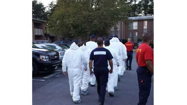 The Prince George's County Police Department's academy glass wears protective gear to search for evidence.
