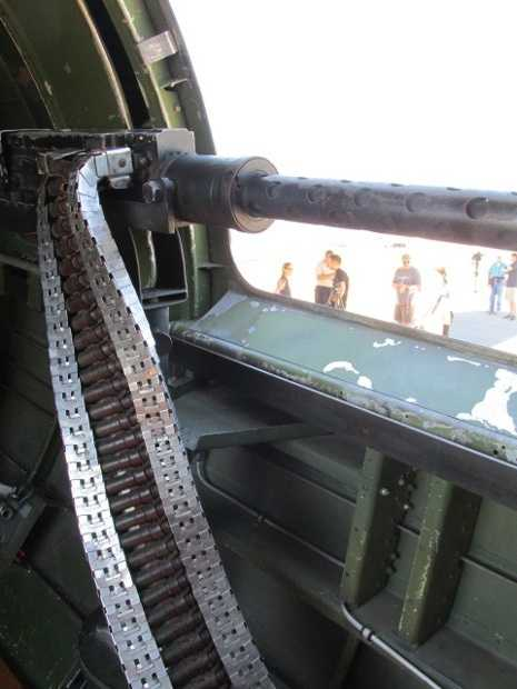 Up-close view of the waist gunner artillery, with a view of the crowd outside.