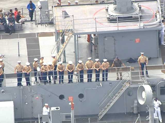 Jason Newton hangs with sailors as the ship moves into the Inner Harbor.