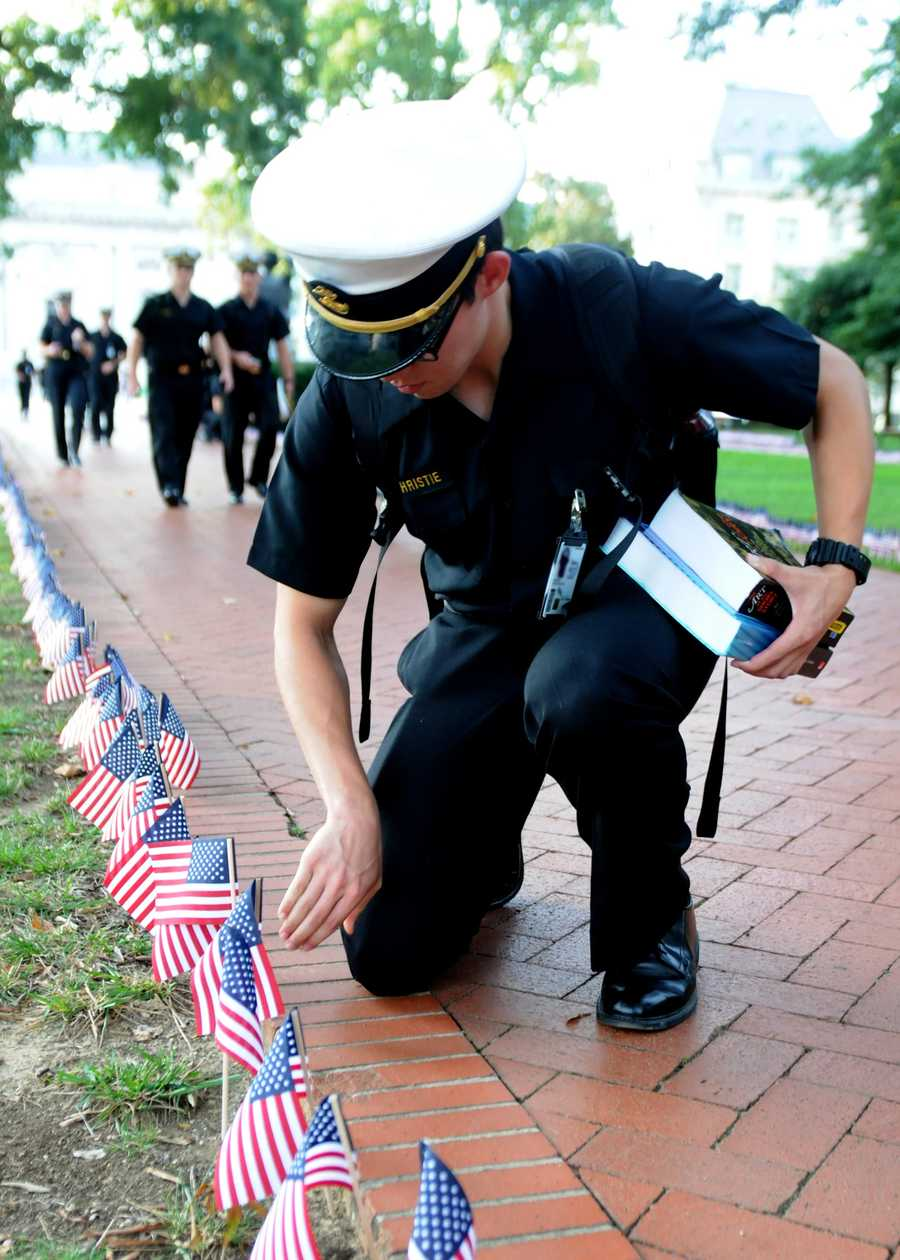 Midshipman 4th Class David Christie places an American flag along Stribling Walk at the U. S. Naval Academy.