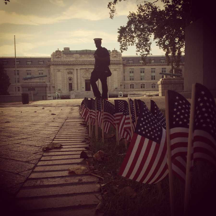 A midshipman pauses along Stribling Walk at the U.S. Naval Academy, where 2,977 American flags were placed to commemorate the lives lost on Sept. 11, 2001.