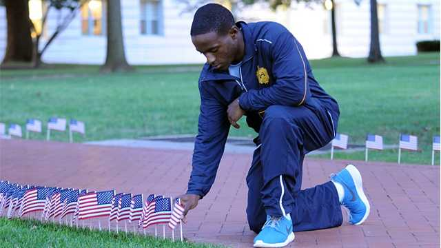 Midshipman 2nd Class Chad J. Rogers places an American flag along Stribling Walk the U. S. Naval Academy.