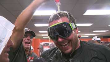 Pitcher Tommy Hunter smiles as he's drenched in beer by fellow players.