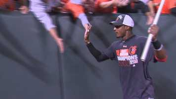 Adam Jones gives high-fives to fans as he rounds the stadium during the celebration.