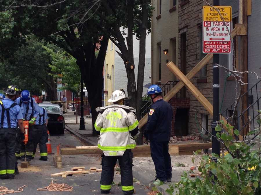 Firefighters assemble timbers to shore up the structure