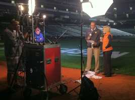 Mindy Basara and Jason Newton on the field before sunrise during live broadcast of WBAL-TV 11 News Today.