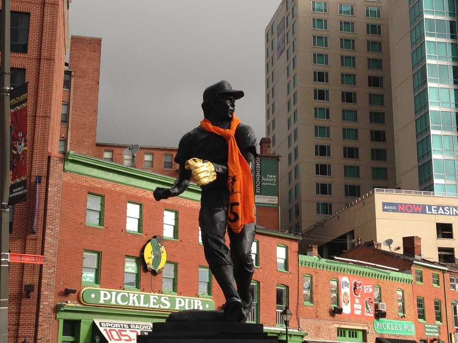 The Brooks Robinson statue is adorned in baseball gear and O's colors for the ALDS.