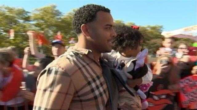 Nelson Cruz carries his daughter past the crowd.
